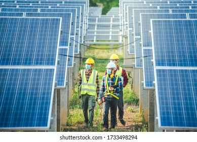 A team of engineers and three Asian architects walked to visit the solar panel. Engineering team wearing medical masks to protect the corona virus (Covid-19). Asian engineers look at solar panels.