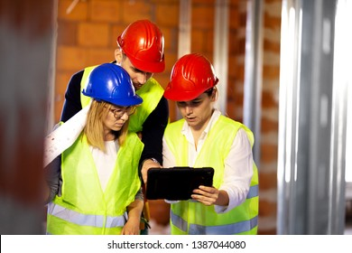 team of engineers with vests and hard hats looking in a tablet, on a construction site