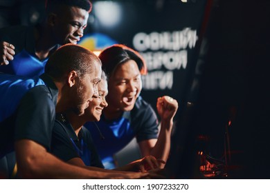 Team of excited professional cybersport gamers looking at PC screen and celebrating success while participating in eSport tournament. Playing online video games