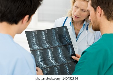 Team Of Experts Doctors Examining X-ray Report In Hospital