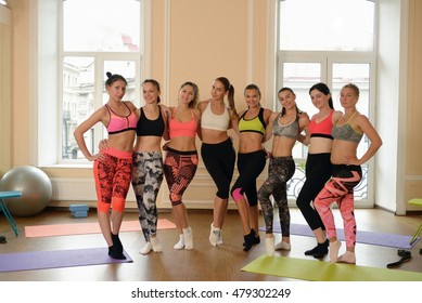 Team of fitness girls poses together after training