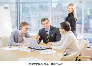team of four business people discussing an important question at briefing