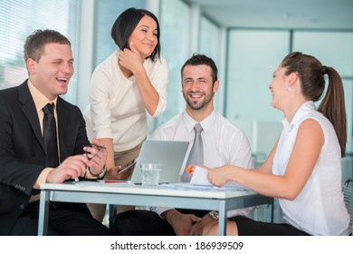 Team of four business people smiling in office