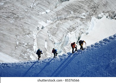 A team of four climbing on the ridge of snowy mountain