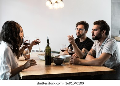 Team of friends chatting at dining table, drinking wine, eating snacks. Young men and women in casual meeting indoors. Friendly dinner concept