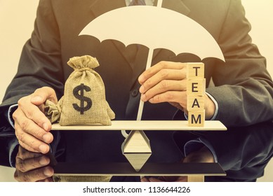 Team fringe benefit or money incentive protection concept : Businessman holds a white umbrella, protects or guards a US dollar bag on a balance scale, depicts a reward for completing exceptional work
