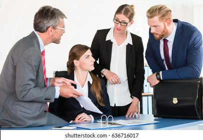 Team gathers around a desk, discussing a document