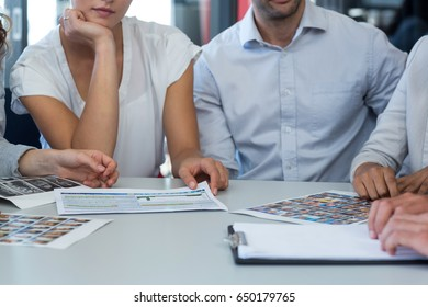 Team of graphic designers discussing over photos in office
