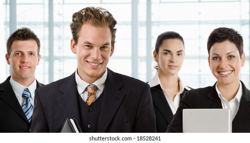 Team of happy business people, smiling businessman in front.