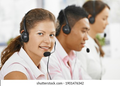 Team of happy customer service representatives sitting in a row wearing headsets. Young woman in front looking at camera, smiling.