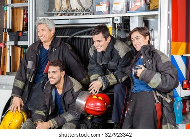 Team of happy firefighters looking away by firetruck at station