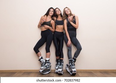 Team of happy fitness friends. Three girlfriends posed in kangoo jumping shoes. Sport girl standing on wall background in kangoo jumping shoes.