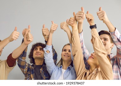 Team of happy people raising hands in air and giving thumbs-up all together. Group of young motivated men and women doing like gesture and smiling. Student teamwork, good job and success concept