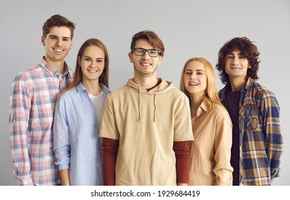 Team of happy young people in casual wear standing on gray studio background. Group portrait of 5 smiling high school friends, college buddies or university students looking at camera all together