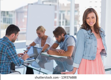 Team having meeting with one woman standing and smiling at camera in bright office
