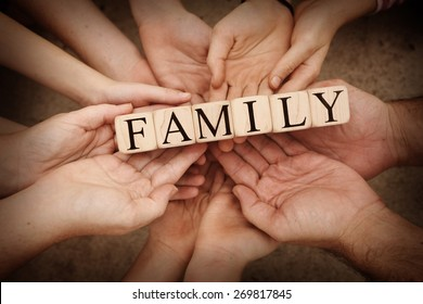 """Team Holding Building Blocks spelling out """"Family"""""""