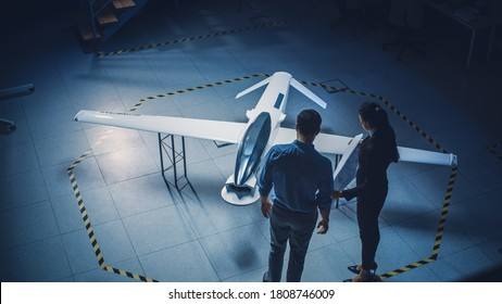 Team of Industrial Aerospace Engineers Work On Unmanned Aerial Vehicle Concept. Designers Work on Pilotless Drone. Industrial Facility with Aircraft Capable of Surveillance and Military. Elevated Shot