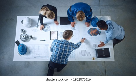 Team of Industrial Engineers Lean on Office Table, Analyze Machinery Blueprints, Architectural Problem Solving, Consult Project on Tablet Computer, Inspect Metal Component. Flat Lay Top Down View