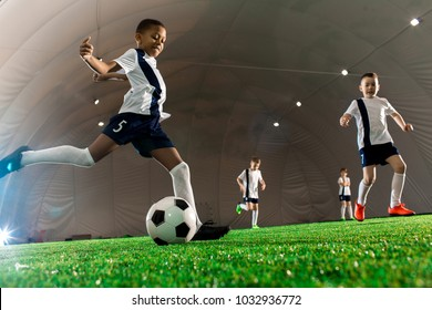 Team of intercultural boys running throughout football field, one of them kicking the ball