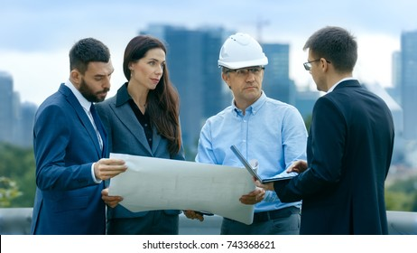 Team of Investors, Developers and Engineers Discuss Future of the Major Real Estate Project  with Major Contractor while Consulting Drafts and Plans. In the Background Big City with Skyscrapers.
