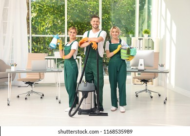 Team of janitors with cleaning supplies in office