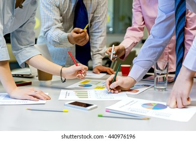 Team Job Business Concept Group of People discussing new start up Project in modern Office loft. Printed Charts dropped around on grey Table