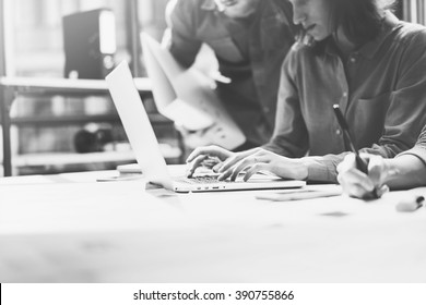 Team job. Photo young businessmans crew working with new startup project in modern loft. Generic design notebook on wood table. Horizontal, film effect, black and white