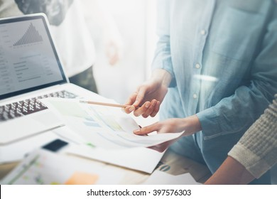 Team job succes.Closeup photo young business managers  working with new startup project in office.Analyze document, plans. Contemporary notebook on wood table, papers, documents. Horizontal, blurred