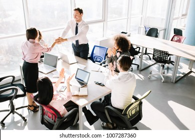 Team lead shakes manager hand because of good job. Other managers clapping.