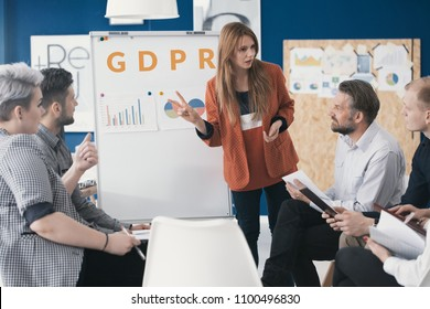 Team leader explaining the new General Data Protection Regulation to her employees in the meeting area of a company building.