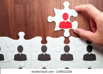 Team leader and leadership concept. Appointing to leader.Human resource management. Assembling jigsaw puzzle on wood desk.