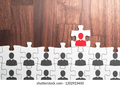 Team leader and leadership concept. Standing together.Business teamwork. Assembling jigsaw puzzle on wood desk.