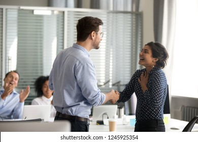 Team leader motivating handshaking female Indian excited employee, congratulate with promotion, business achievement, thank for good result, work, expressing respect, support, colleagues applaud
