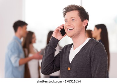 Team leader on the phone. Handsome young man talking on the mobile phone and smiling while group of people communicating on background