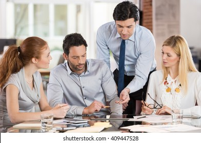 Team leader pointing charts and graphs on digital tablet. Businesspeople working as a team in the office. Businesspeople working together and discussing about new ideas for marketing.
