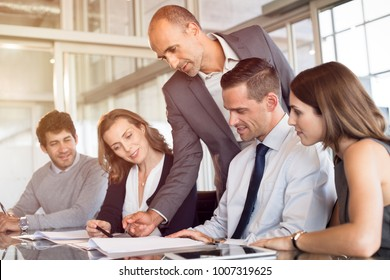 Team leader pointing at report during meeting with his colleagues. Business team working together in modern office. Young minds of office discussing new ideas for marketing with boss.