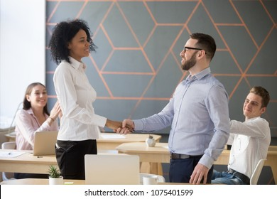 Team leader promoting successful african worker handshaking appreciating for good work results or rewarding, diverse company boss and employee shaking hands expressing gratitude, respect and support