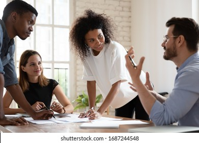 Team leader talk at briefing express point of view to diverse teammates, multiracial young workers brainstorming in board room discuss new project, process of negotiations at business meeting concept