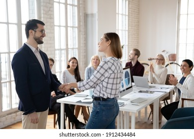 Team leader thanking best employee for work achievements. CEO and manager shaking hands. Staff welcoming and applauding new hired employee in conference room. Recognition, acknowledgement concept