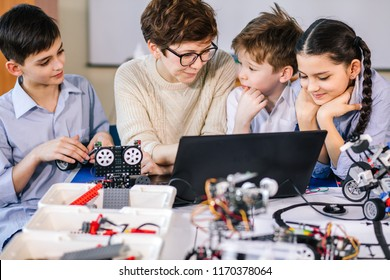 Team of little curious technicians working together with their teacher in robotics class