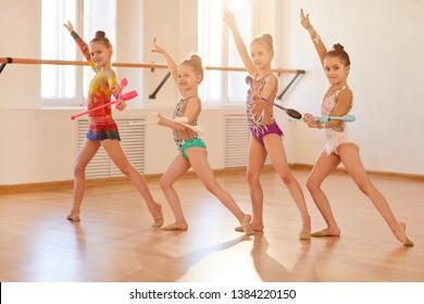 Team of little girls practicing rhythmic gymnastics with clubs,