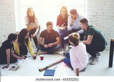 Team of male and female students in casual clothing working together on sketch of building planning during training.Young crew of engineers collaborating on solving problems in office interior