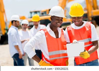 Team of male workers at a building site looking happy