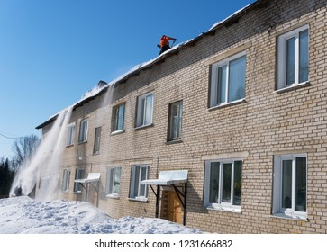 The team of a male worker's clean roof of building from the snow with shovels. Danger of falling snow and icicles on the head.