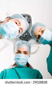 Team of medical doctors looking down at patient in surgical theater