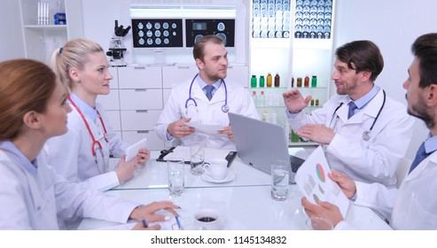 Team of Medical Doctors Positive Talking About Pie Chart Report Expertise in Hospital Meeting Room
