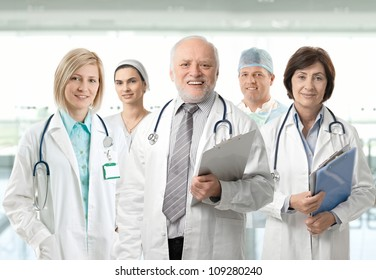Team of medical professionals lead by senior white haired doctor looking at camera, smiling.