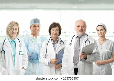 Team of medical professionals looking at camera, smiling in hospital lobby.
