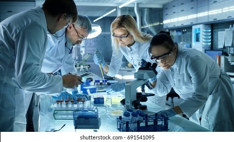 Team of Medical Research Scientists Collectively Working on a New Generation Experimental Drug Treatment. Laboratory Looks Busy, Bright and Modern.
