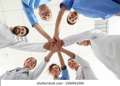 Team of medical workers holding hands together in hospital, bottom view. Unity concept
